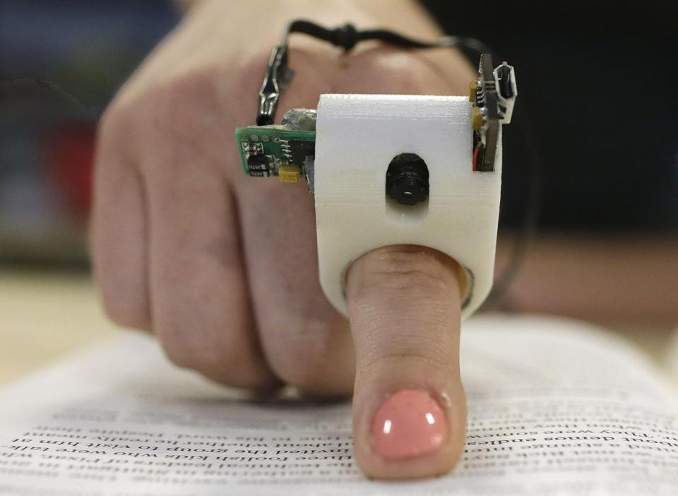 A model wears a FingerReader ring at the MIT Media Lab in Cambridge. Researchers designed and developed the instrument, which enables people with visual disabilities to read text printed on paper or electronic devices. Electronic instructional materials may create barriers for the visually impaired.