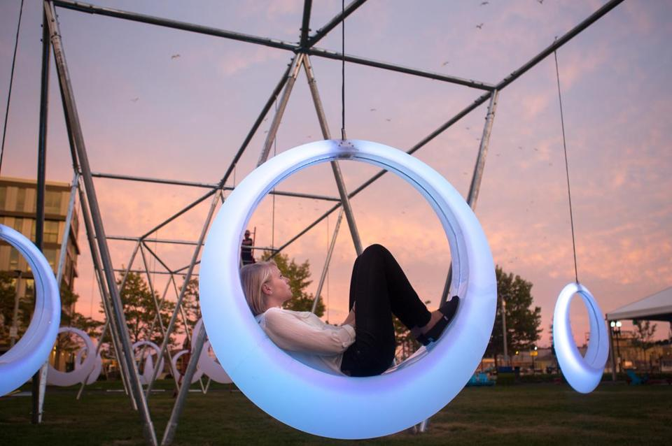 Sep. 8, 2014 - Anna Kaertner, an intern at Höweler + Yoon Architecture sits in an illuminated swing part of an art installation outside the Boston Convention and Exhibition Center in Boston, Mass. which was designed by Höweler + Yoon. (Justin Saglio for The Boston Globe)