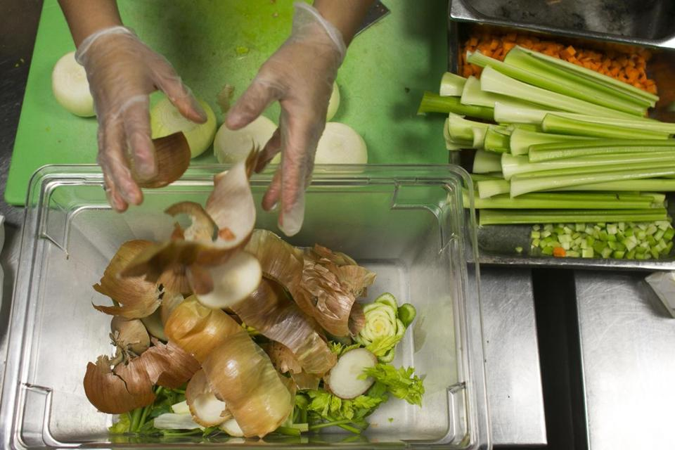 August 10, 2014 Boston, MA - City Table at the Lenox Hotel Eliza Martinez preps onions in the kitchen and places all compostable waste in a plastic tub which she later transfers to an organic waste barrel (Katherine Taylor for The Boston Globe)