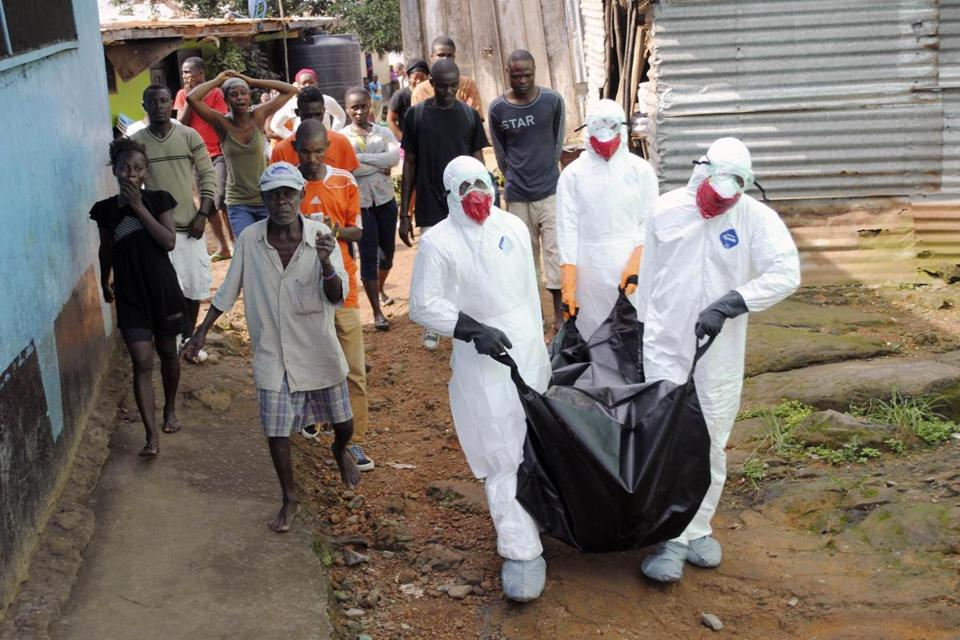 Health workers in Liberia removed the body of an Ebola victim. A Boston organization is sending staff to help in rural parts of the country.