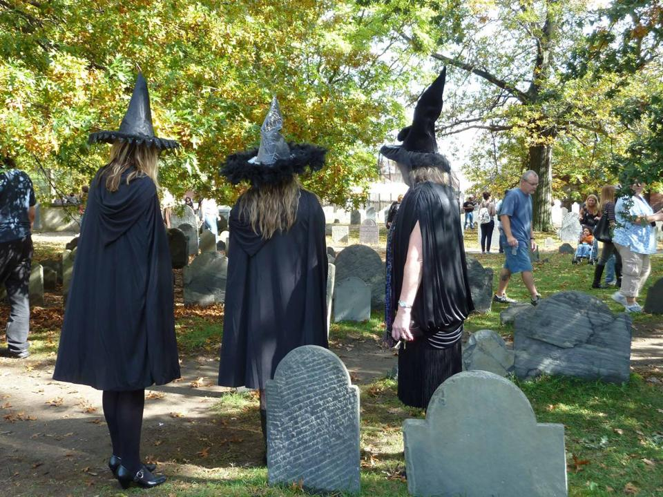 Visitors in witch hats inspect the old gravestones in Charter Street Cemetery in Salem.