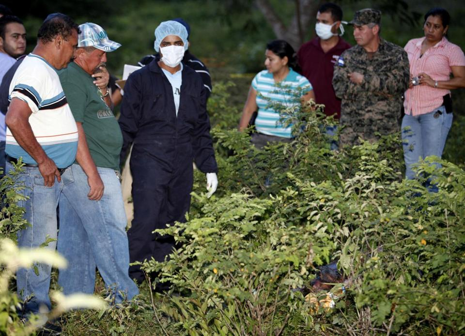 Forensic workers, relatives, and law enforcement officials stood next to the site where the body of TV reporter Herlyn Espinal was found in San Pedro Sula, Honduras, in July.