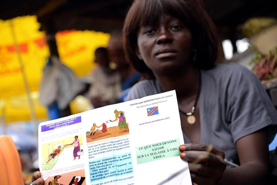 A vegetable seller held a leaflet on Ebola from the Congolese Ministry of Health.
