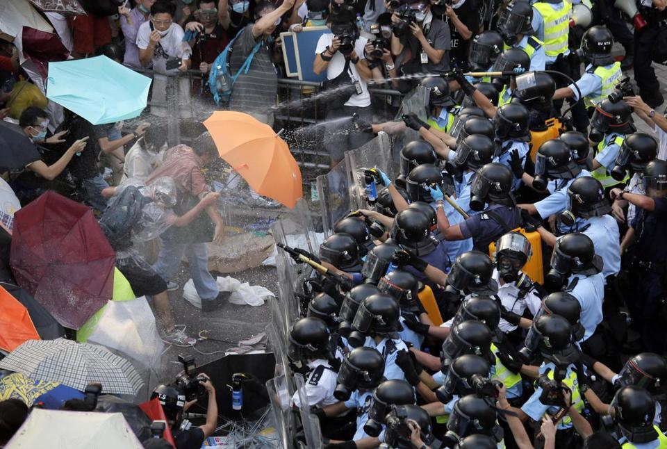 Riot police use pepper spray against protesters in Hong Kong on Sunday.