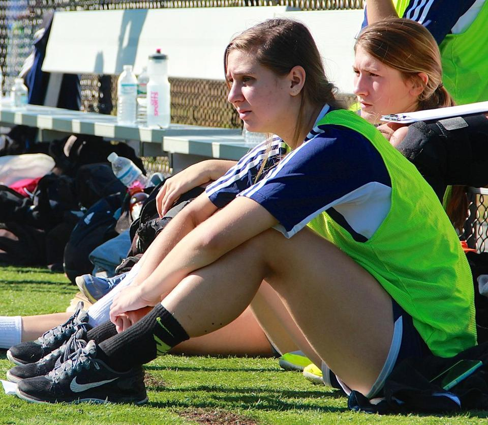 Needham's Rachel Kingston watches her teammates from the sidelines.