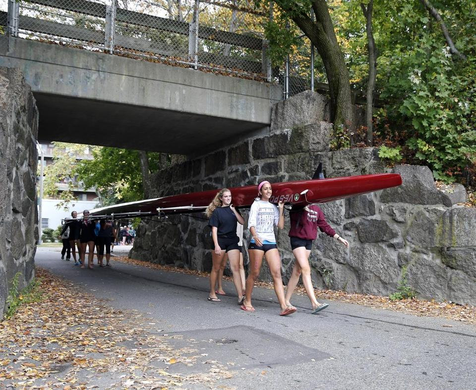 Members of the Arlington-Belmont boys' and girls' crew teams carry their boats to practice in Arlington. Above middle: Olivia Ferreira gets some practice in and coach Laura Rothman yells instructions through a megaphone.
