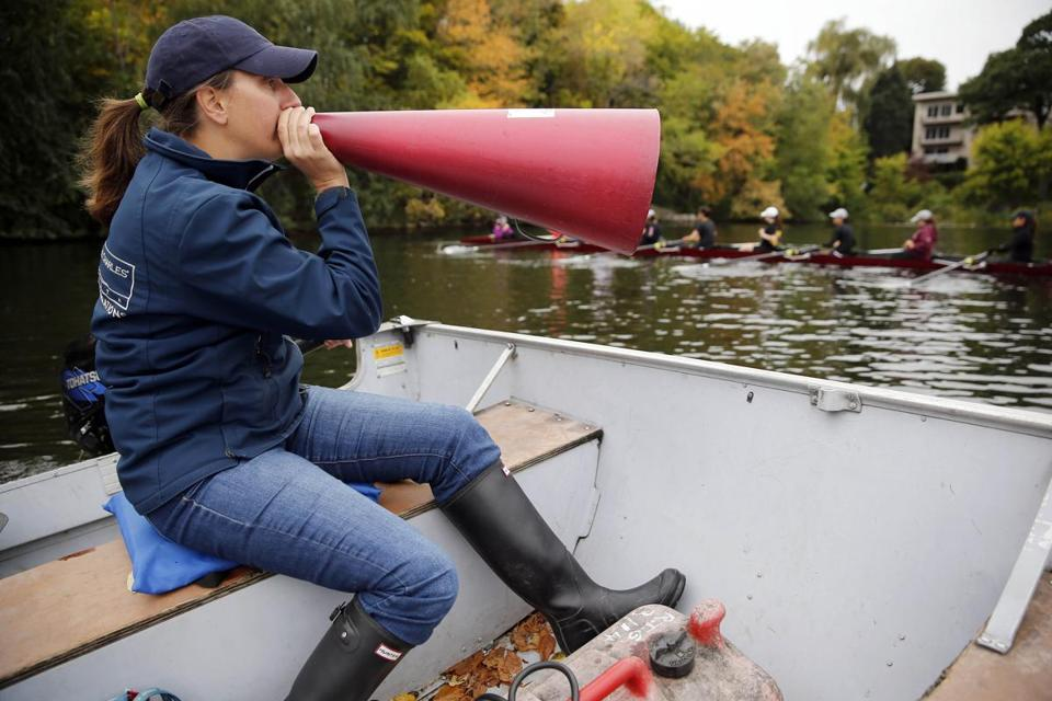 Arlington-Belmont girls coach Laura Rothman directs crew team members through a megaphone during practice.