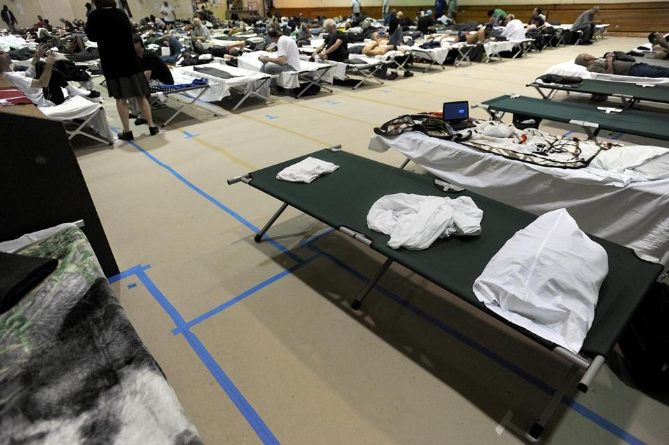 Cots lined the basketball court at the South End Fitness Center, a temporary shelter for former Long Island residents.