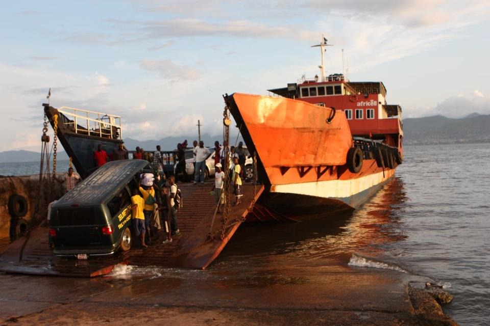 A crowd gathered to lend a hand after a van became stuck while exiting a ferry in Sierra Leone.