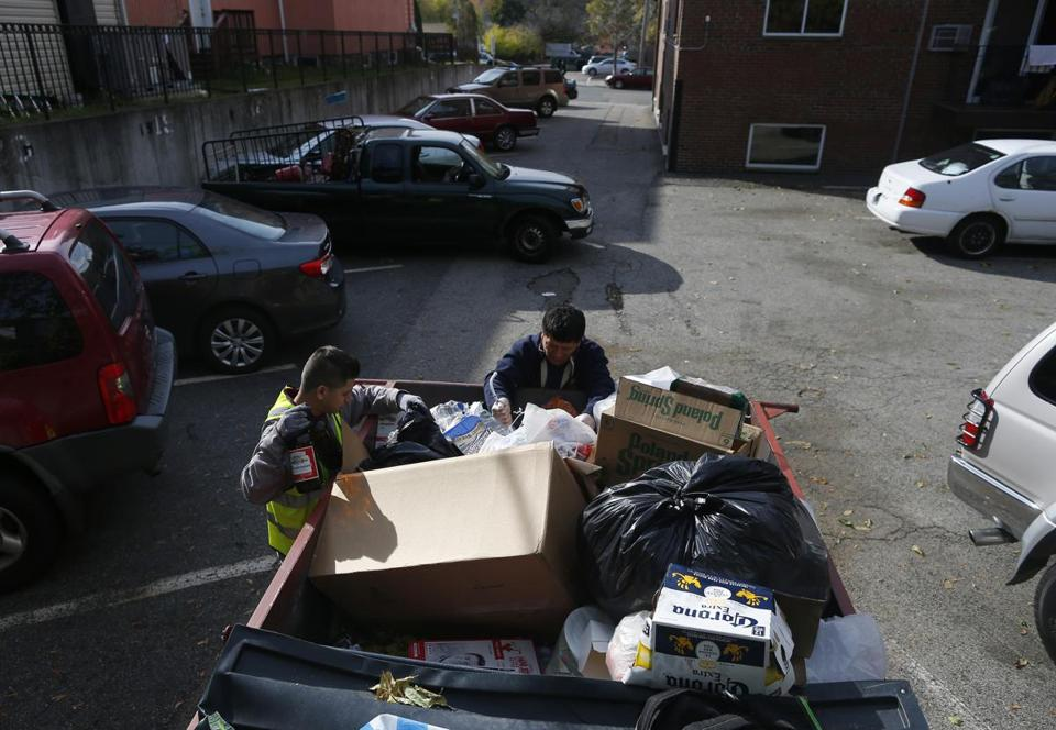 Jose Lopez, 23, (left) and his father, Reynabel Lopez, 46, of Allston looked through a dumpster in Brighton for cans and bottles to redeem for cash.