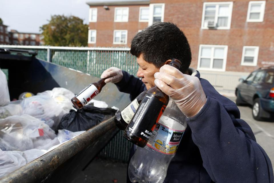 Reynabel Lopez, collecting bottles from a dumpster in Brighton, regularly patrols the city for recyclable cans and bottles. An expanded deposit law would benefit those who collect.
