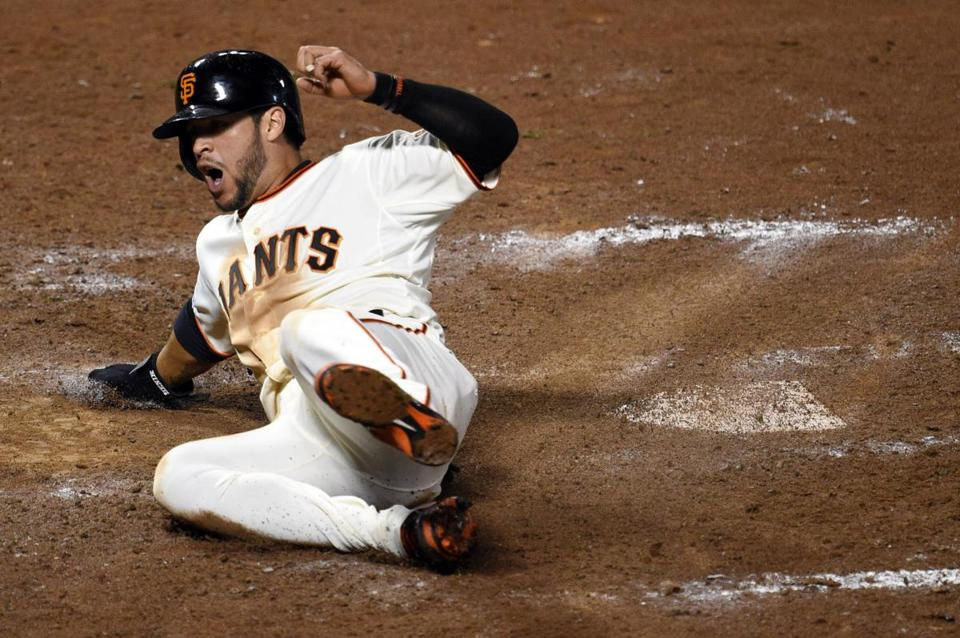 Gregor Blanco slides across with another Giants run in the seventh inning of Game 4 on Saturday night. (Ed Szczepanski/USA TODAY Sports)
