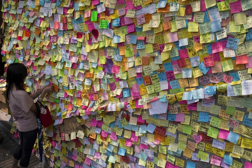 A woman adds a piece of paper to a wall with a message of support for pro-democracy demonstrations.