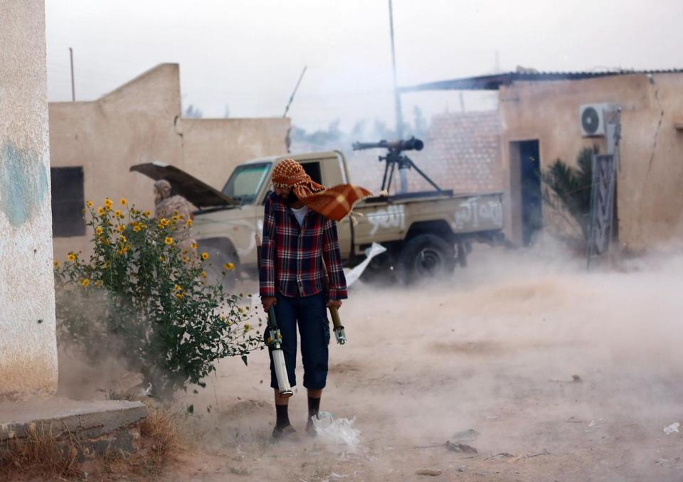 Pro-government militia fighters with Libya's Shield Brigade fired an anti-tank cannon mounted on a pick-up truck during clashes with gunmen accused of being loyal to the former regime of slain dictator Moammar Khadafy on Sept. 16 in a suburb of Tripoli.