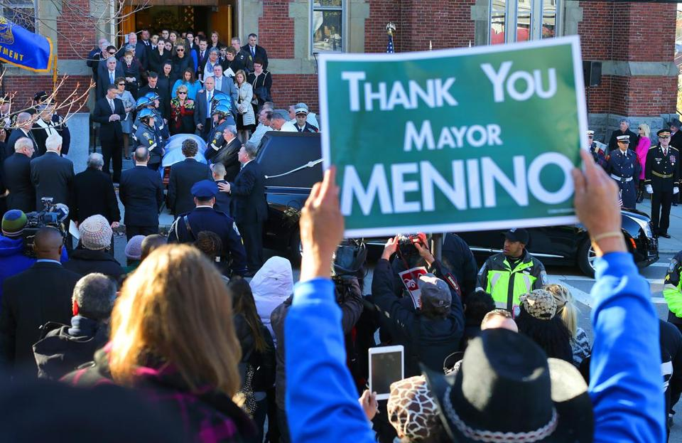 Carlos Arredondo held a sign thanking Thomas Menino as the former mayor's casket was brought out after a funeral Mass Monday.