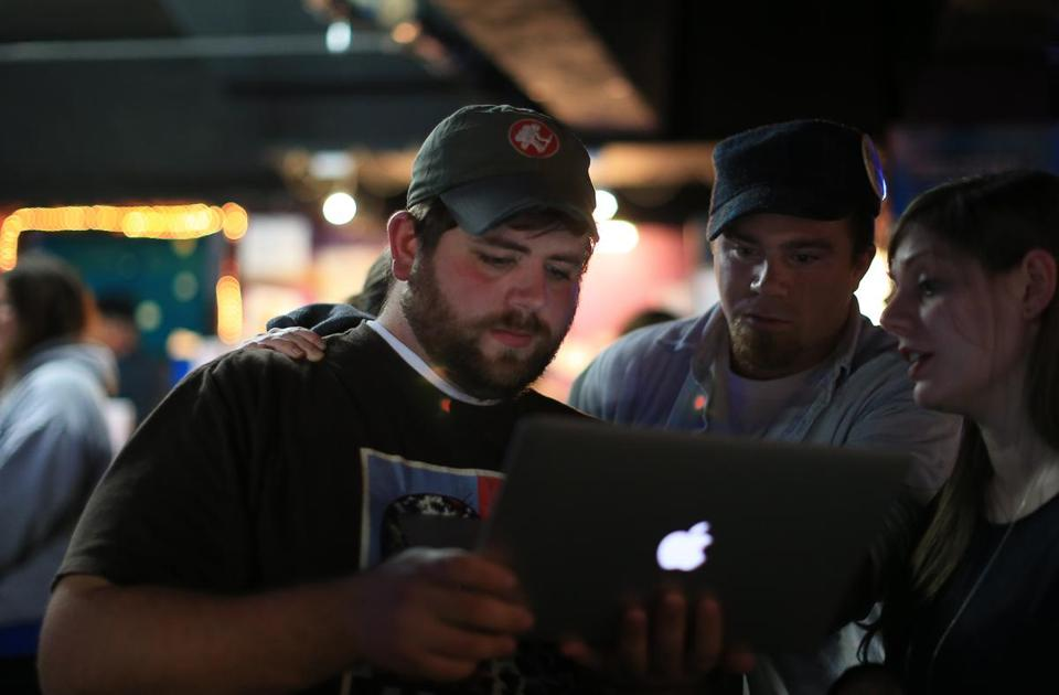 Joseph Catricala, left, John Rogers, middle, and Elizabeth Fitzgerald looked at the disapointing results of their caasino repeal efforts, while at Pockets Billiards Club in East Boston.