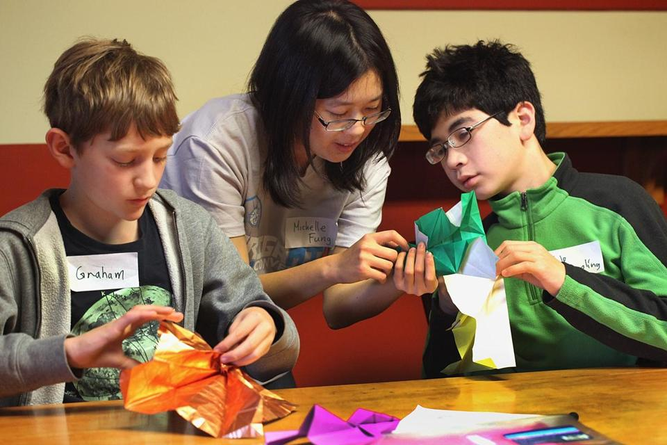 Michelle Fung lent her expertise to Graham Stearns (left) and Cole Eppling as they created yellow jackets at OrigaMIT.