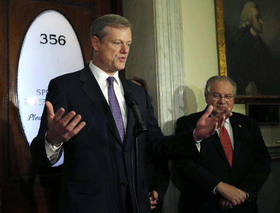 Massachusetts Governor-elect Charlie Baker spoke to reporters at the Statehouse Monday as House Speaker Robert DeLeo listened, at right.