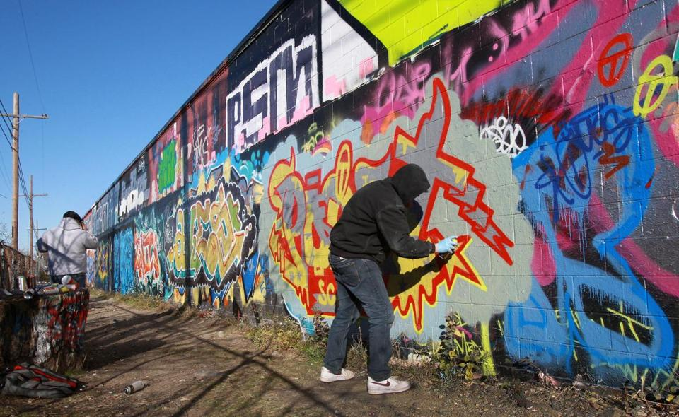 Artists worked at the Clemenzi Industrial Park in Beverly. Since people began spraypainting the wall a decade ago, the drawing of graffiti has fallen elsewhere in the city.