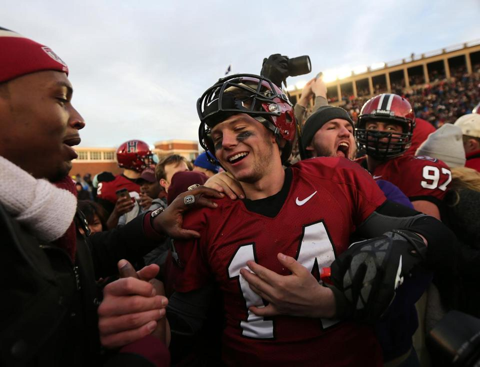 Crimson quarterback Conner Hempel (14) is at the center of the onfield celebration after Harvard defeated Yale, 31-24. Barry Chin/Globe Staff