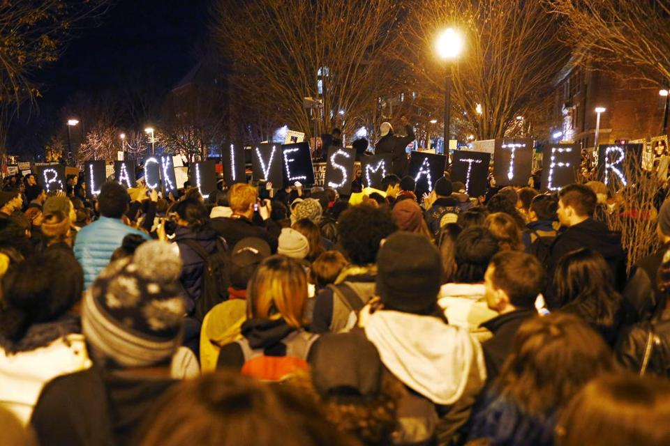 "Demonstrators held lighted signs spelling out ""Black Lives Matter"" during a protest in Boston."