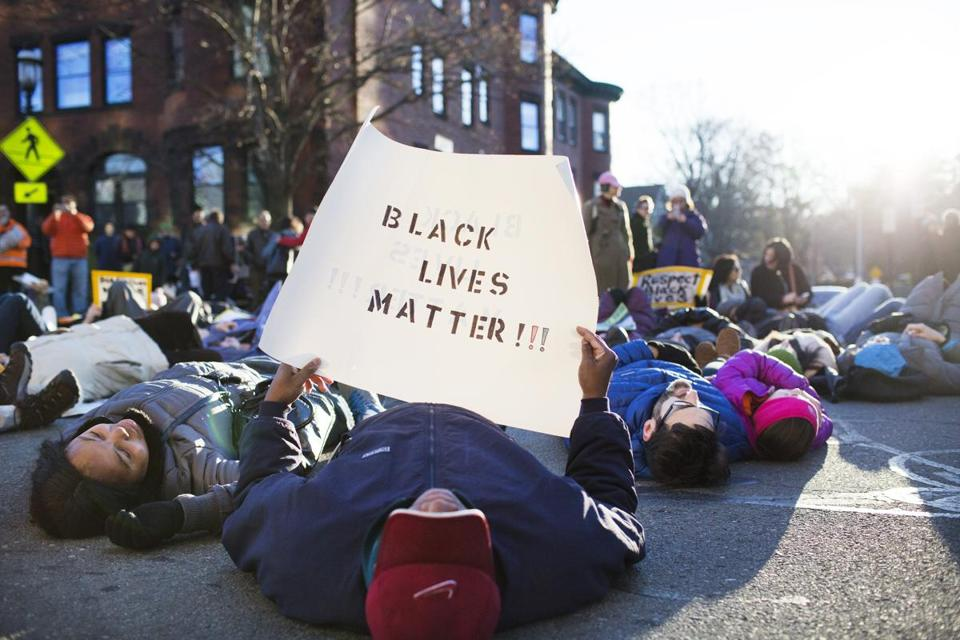 "Brookline residents staged a ""die-in"" outside the Brookline Police department on Sunday in support of the growing movement Black Lives Matter."
