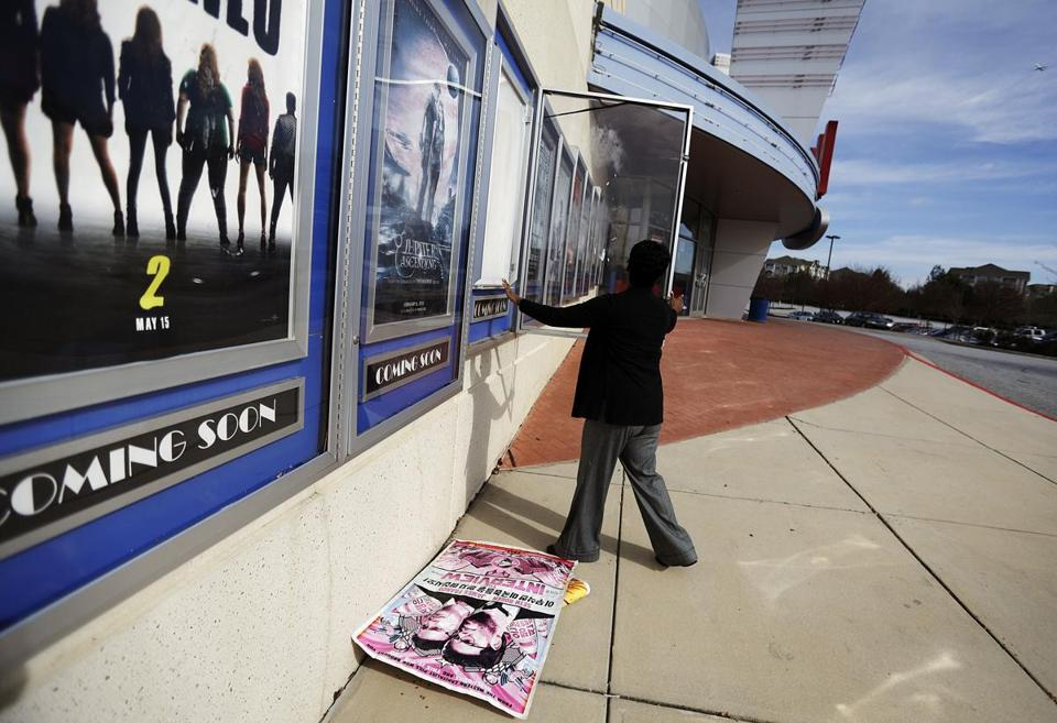 "A poster for the movie ""The Interview"" is pulled from a display case by a worker at a Carmike Cinemas movie theater in Atlanta."