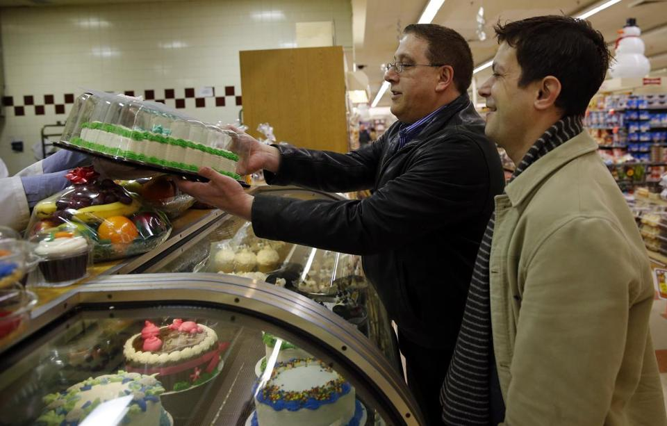 Tim Coco (left), and Genesio Oliveira, married since 2005, bought a cake at the Market Basket in Plaistow, N.H., to celebrate Oliveira's long-awaited permanent residency.