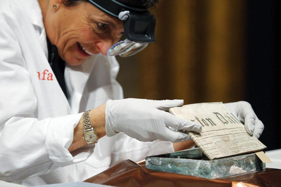 Pam Hatchfield removed a newspaper from a State House time capsule in January.