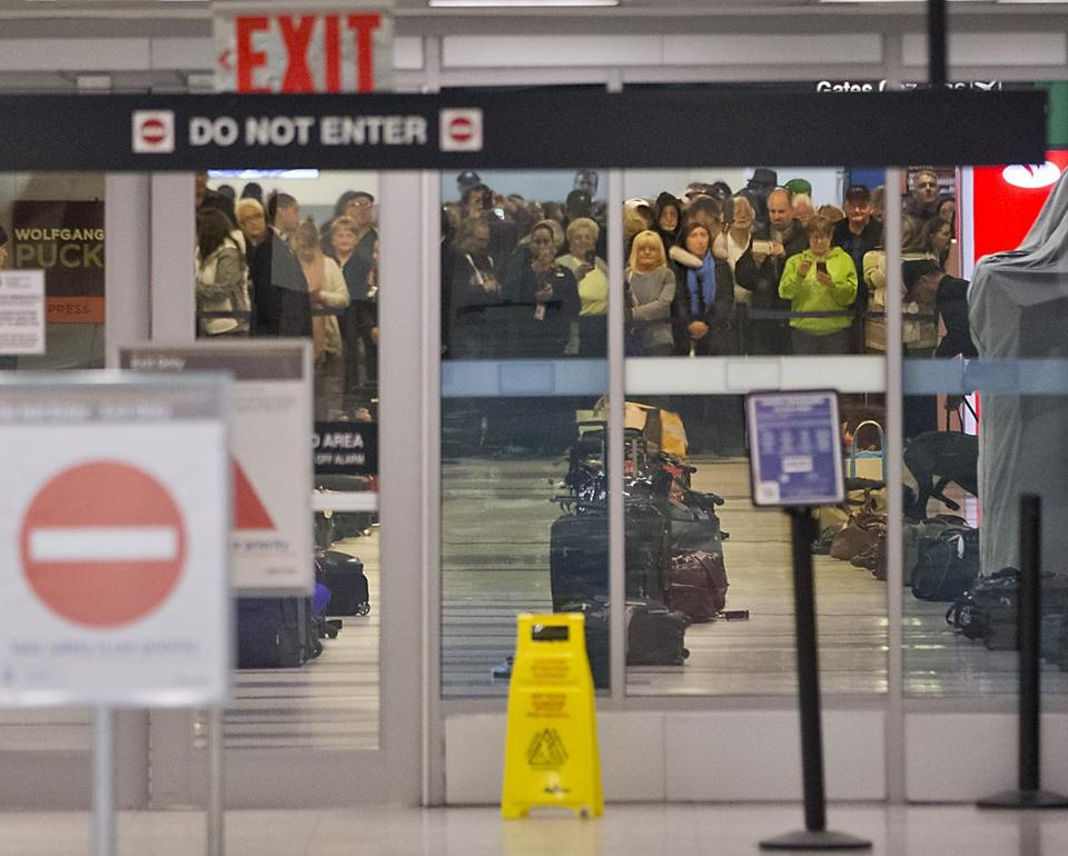 JetBlue passengers watched as a State Police bomb squad, assisted by explosives-sniffing dogs, searched their carryon luggage following a bomb threat Monday night.