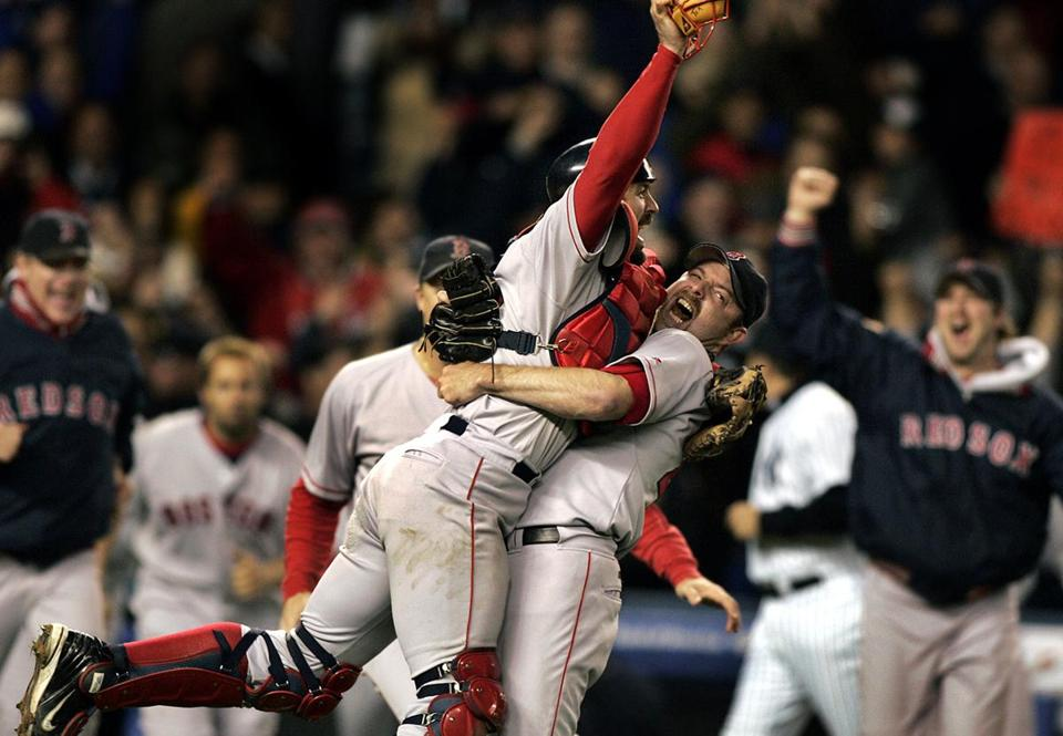 10-20-2004:New York, NY:GLOBE STAFF PHOTO/JIM DAVIS.................Red Sox catcher Jason Varitek and pitcher Alan Embree embrace as the rest of the Boston players rush out of the Yankee Stadium dugout to begin the celebration following the final out of the Game Seven of the ALCS victory that sent them to the World Series. outtakes