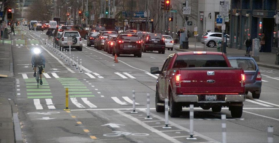 "Seattle's Second Avenue bike track is separated from busy downtown traffic by white plastic posts, or ""bollards."""