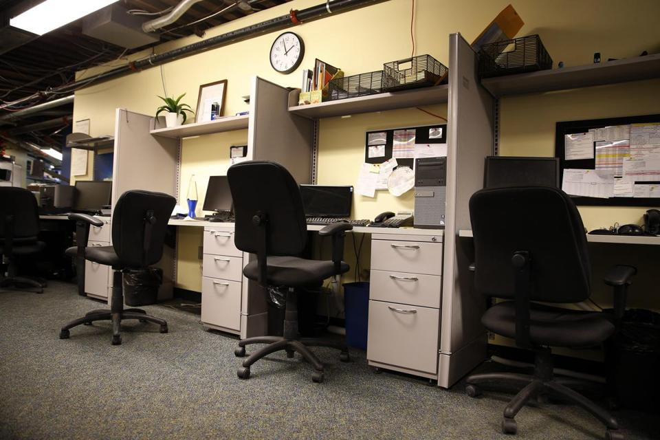Empty cubicles, as at Boston Business Printing on Tuesday in Boston, place a strain on businesses. Jessica Rinaldi/Globe Staff
