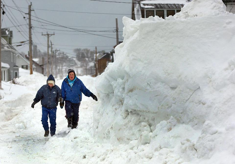 Pedestrians try to avoid the huge snow accumulations in Hull.