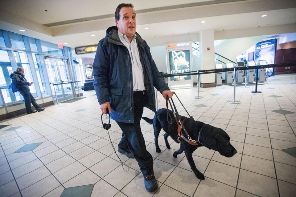 "Carl Richardson and his service dog enter AMC Loews Boston Common Theater to take in ""American Sniper."" Richardson received a special hearing device to enjoy the film."