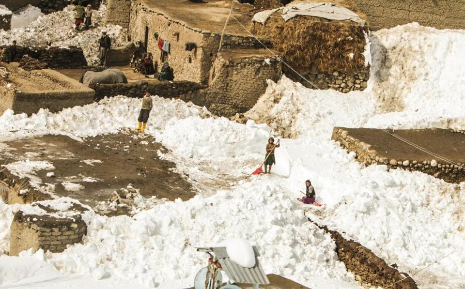 People stood on the roof tops Saturday after a huge avalanche, in Paryan district of Panjshir province, Afghanistan.