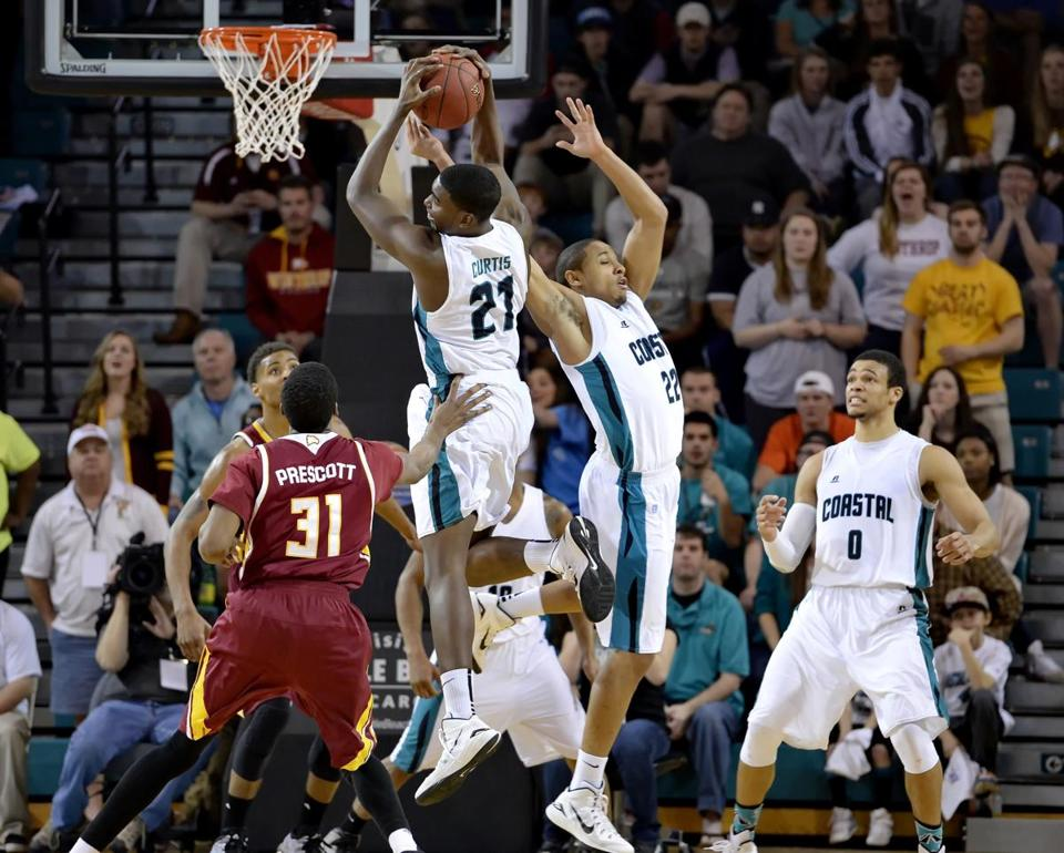 Coastal Carolina's Tristian Curtis, center, and Elijah Wilson, center right, go up for a rebound while pressured by Winthrop's Tevin Prescott during the second half of the Big South Conference Championship NCAA college basketball game Sunday, March 8, 2015, in Conway, S.C. Caolina Coastal won 81-70. (AP Photo/Richard Shiro)