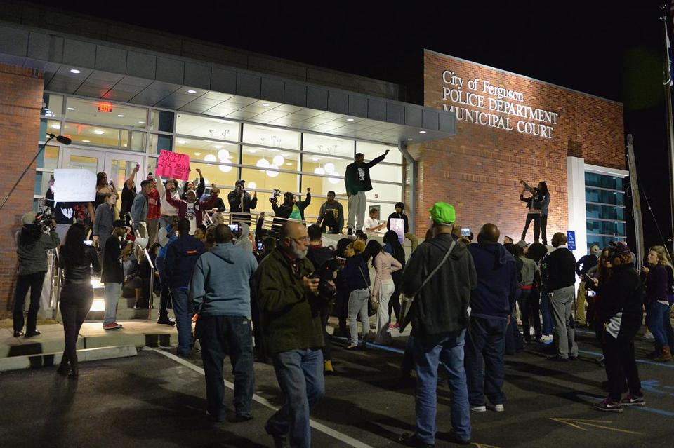 Protesters demonstrated outside the Ferguson, Mo., Police Department on Wednesday after the city manager and police chief had resigned. Shots were later fired upon the crowd, wounding two police officers, according to authorities and news accounts.