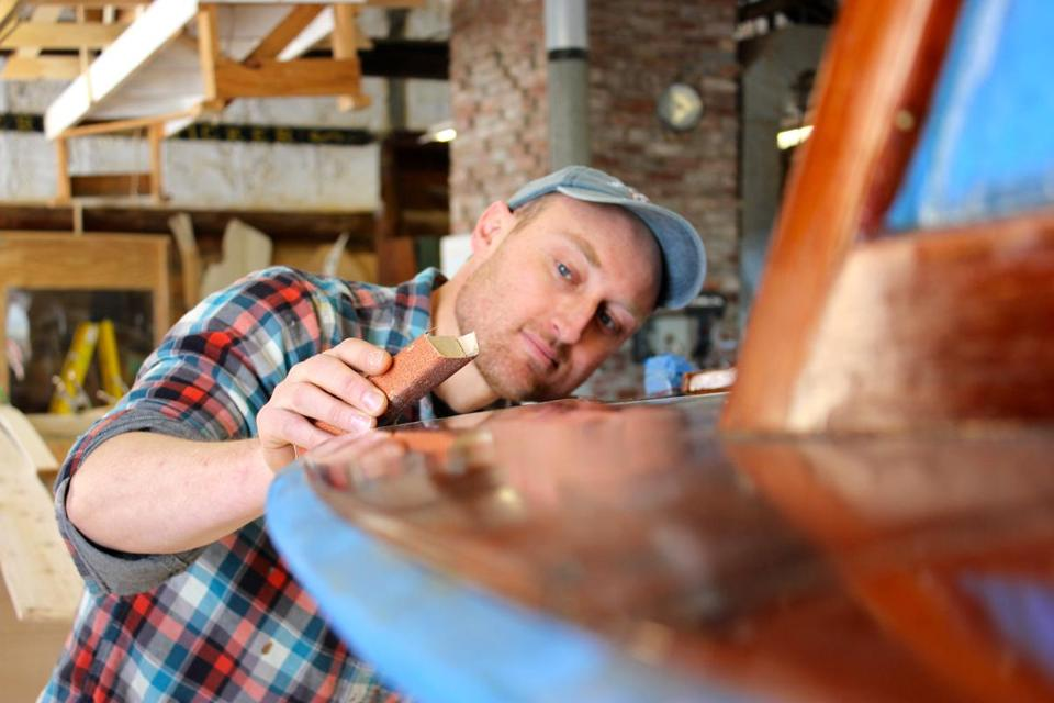 Kurt Spiridakis, boatshop manager at the Maine Maritime Museum sanding a boat in the museum's shop in Bath, Maine. 05muther