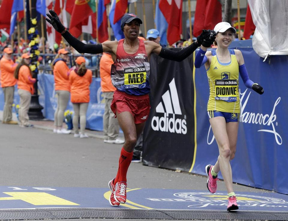 Meb Keflezighi (left) accompanied Hilary Dionne across the finish line at the 2015 Boston Marathon.