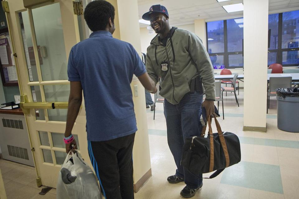 Somali youth Abdinoor Abdille (left) and a Boston police officer, Jean G. JeanLouis, parted after a recent basketball game and talk at the Tobin Community Center.