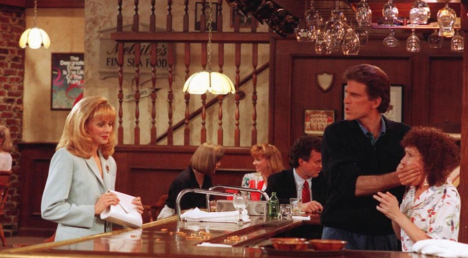 "Shelley Long, Ted Danson, and Rhea Perlman in the TV show ""Cheers."""