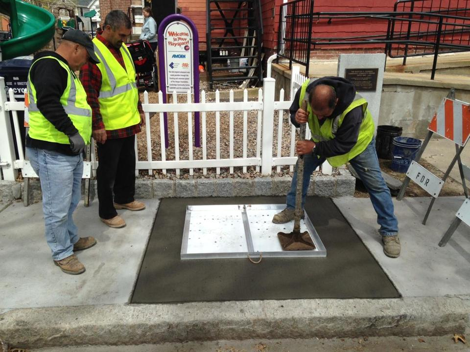 Crew of Fred DeRoma & Son, contractors with the City of Cambridge, applying the Cambridge Poetry Program test stamp in freshly poured concrete on the sidewalk in front of Cambridge Community Center on Wednesday, April 29, 2015. (City of Cambridge)