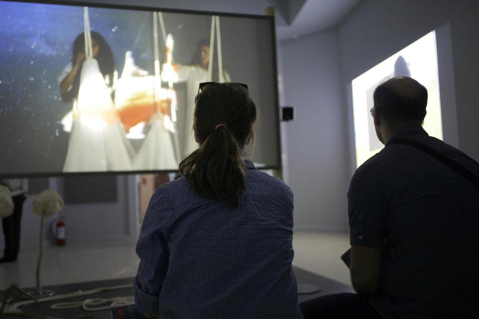 "Visitors looked at the ""They Come to US without a Word' video installation byJoan Jonas."