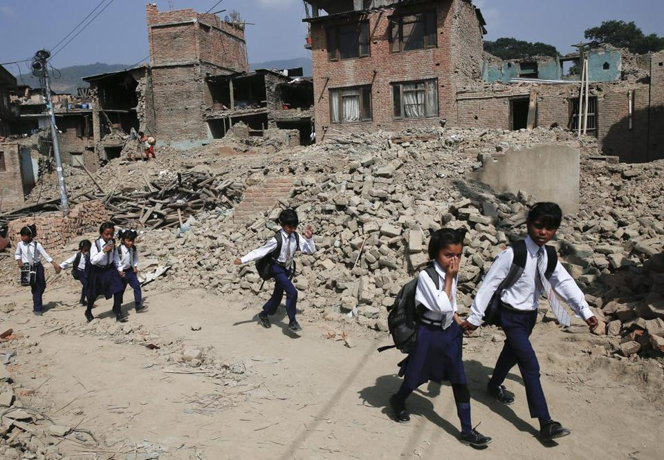 Nepalese children heading to school Sunday passed houses damaged by an April 25 earthquake in Kathmandu.