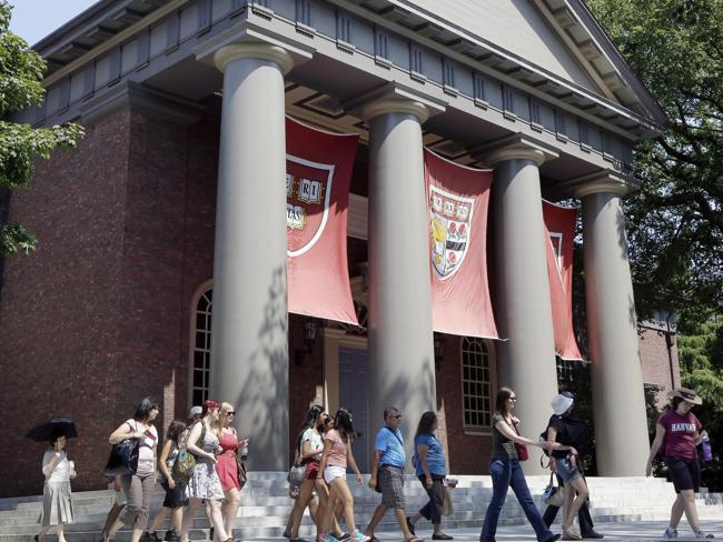 In this Aug. 30, 2012, file photo, a tour group walks through the campus of Harvard University in Cambridge.