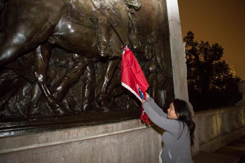 Melissa Carino pulled down a Confederate flag from the Robert Gould Shaw and Massachusetts 54th Regiment Memorial across from the State House on Sunday.