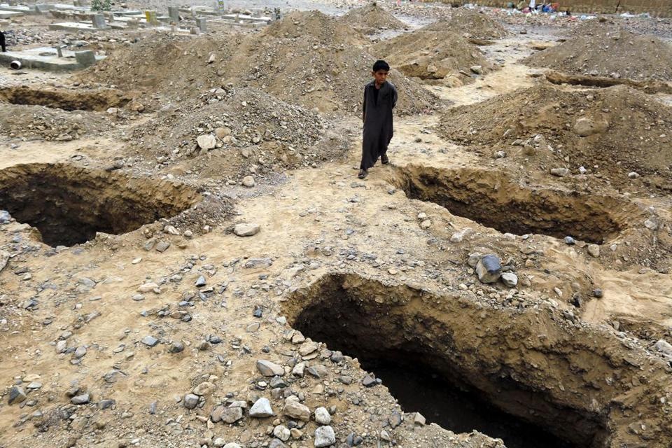 A boy stood over graves Monday after they were prepared for victims of an airstrike allegedly carried out by the Saudi-led coalition in Sana. According to rebel spokesman and medical officials, the area targeted was near a rebel military camp.
