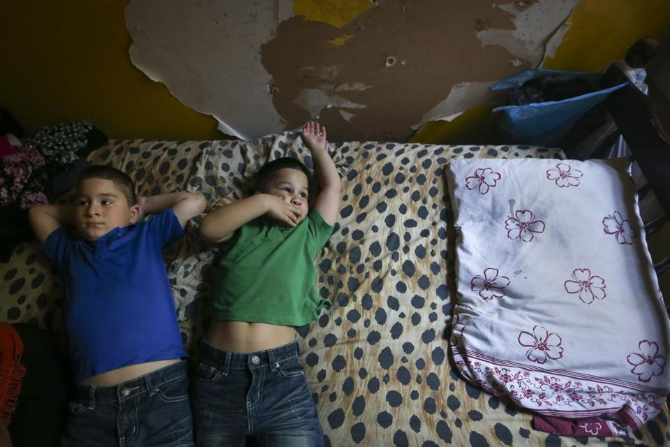 Brothers Jose and William Garcia lay on their bed inside their apartment, where paint peels from the walls.