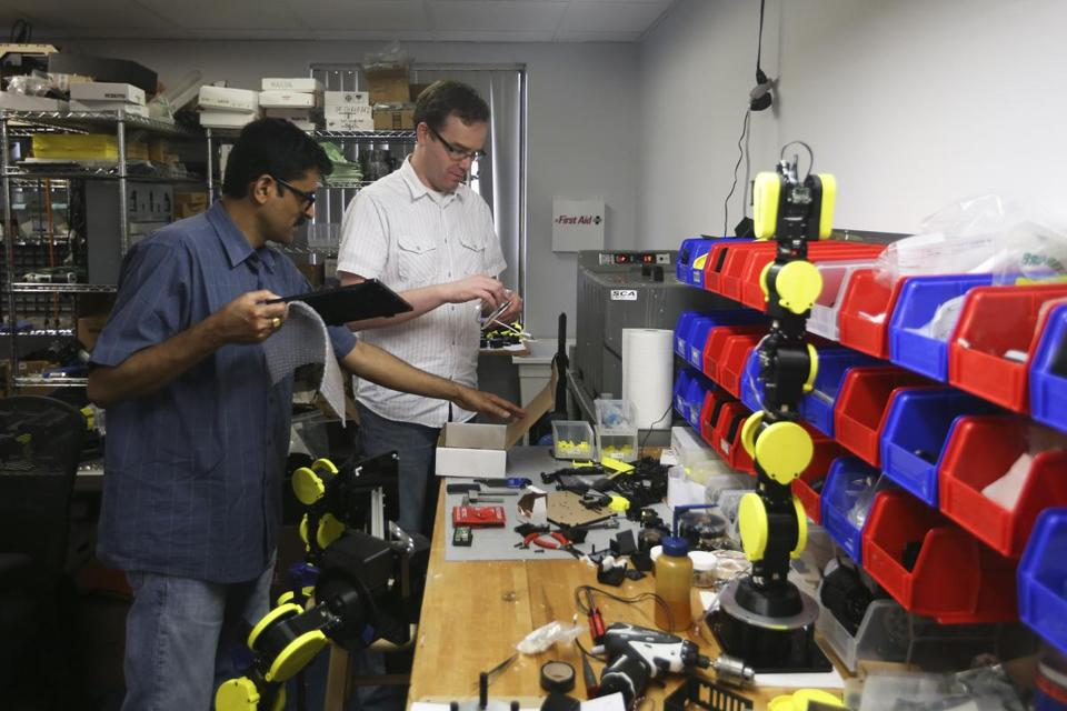 Murphy (left) and Ranjan Mishra organized parts at Energid Technologies in Burlington.